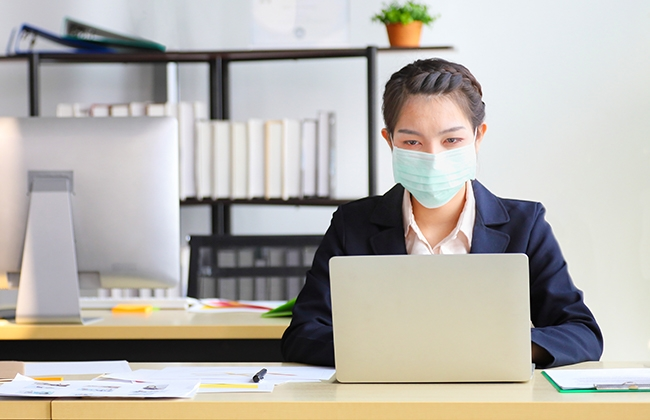 Woman working on computer wearing a mask